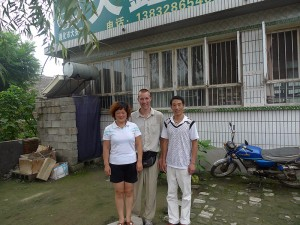 Duan Cai Yan and Wang Hao Zhen in front of their house and pharmacy. See the brick structure to the left? That's the shower.